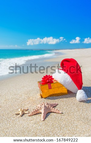 Santa Claus hat and gold christmas gift box on the seashore with sea stars against blue sky - stock photo