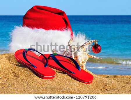Santa Claus hat and slippers on the seashore against blue sky - stock photo