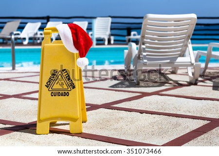 Santa Claus Hat on Wet floor warning sign near a swimming pool - stock photo