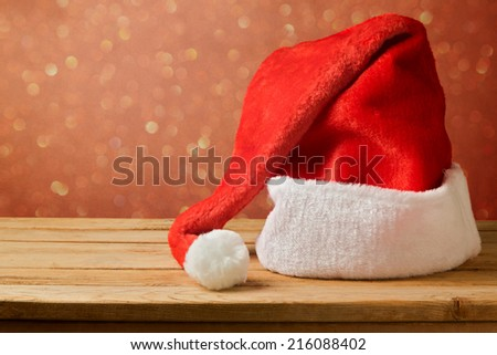 Santa Claus hat on wooden table over bokeh background - stock photo