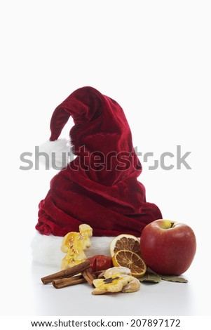 Santa Claus hat with christmas decoration on white background - stock photo