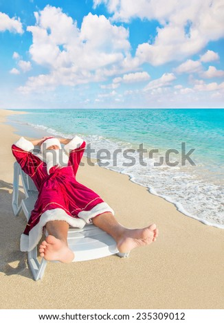Santa Claus have a rest in chaise longue on sea beach - christmas or happy new year concept - stock photo