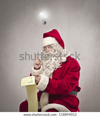Santa Claus have an idea checking the gift list - stock photo