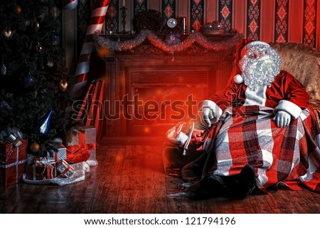 Santa Claus having a rest in a comfortable chair near the fireplace at home. - stock photo