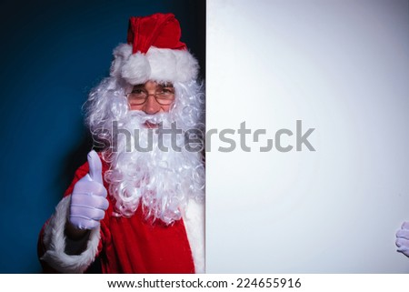 Santa Claus holding a blank board to his left showing the thumbs up gesture. On blue backgroud. - stock photo