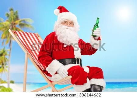Santa Claus holding a bottle of beer and looking at the camera seated on a beach on a sunny day - stock photo