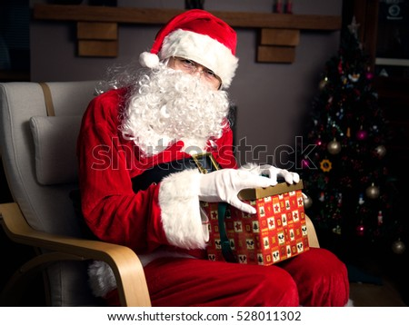 Santa claus holding a gift box in home