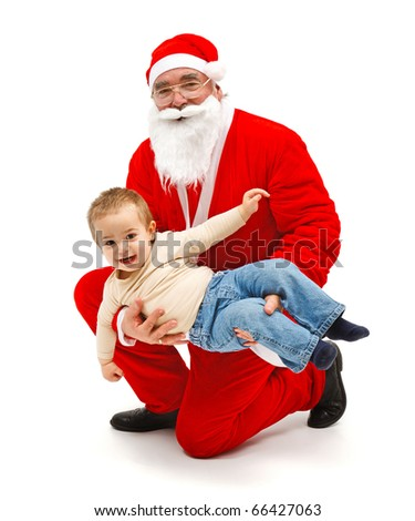 Santa Claus holding a happy, laughing little boy - stock photo