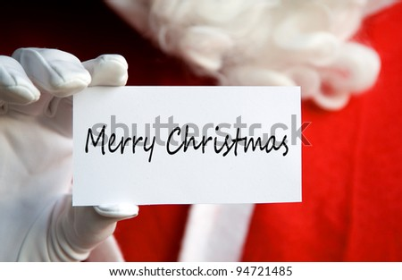 Santa Claus holding a Merry Christmas card in a white gloved hand - stock photo