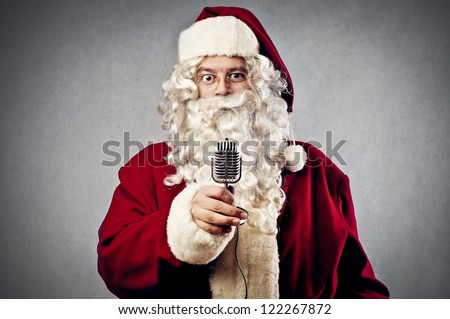 Santa Claus holding a vintage microphone - stock photo