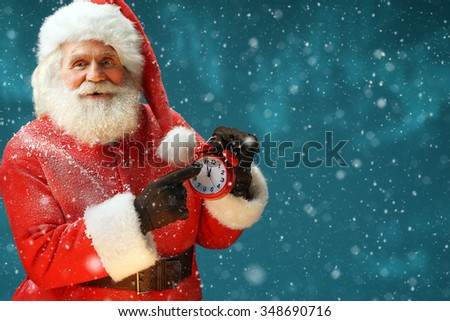 Santa Claus holding alarm. Merry Christmas & New Year's Eve concept / Closeup on blurred blue background.