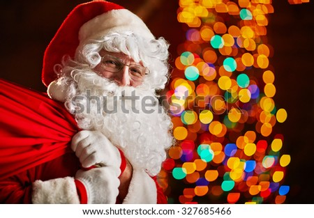 Santa Claus holding big red sack with Christmas gifts - stock photo