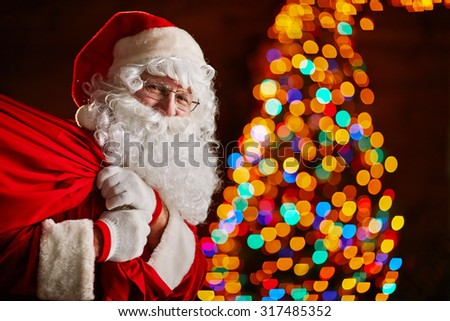 Santa Claus holding big sack with gifts - stock photo