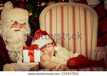 Santa Claus holding Christmas gift box. Child sleeping against Xmas tree. Family holiday concept - stock photo