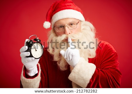 Santa Claus holding clock showing five minutes to midnight and making shhh gesture - stock photo