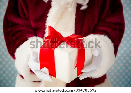 Santa Claus holding gift box in hands. Shallow depth of field  - stock photo