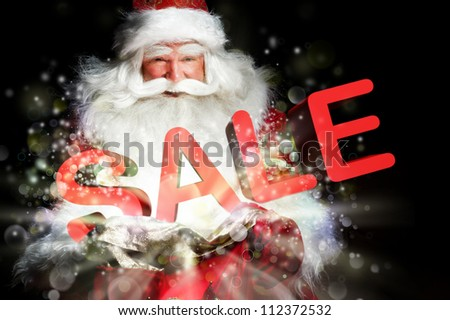 Santa Claus holding his bag and smiling. Lights and sparks are flying from the bag. Sale sign in front of Santa - stock photo