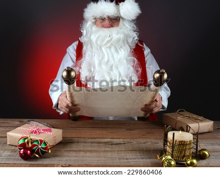 Santa Claus holding his Naughty and Nice list on a scroll of parchment paper. Santa is seated at a wood table with presents and candle, Horizontal format on light to dark red background. - stock photo
