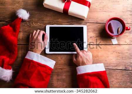 Santa Claus holding tablet in his hands - stock photo