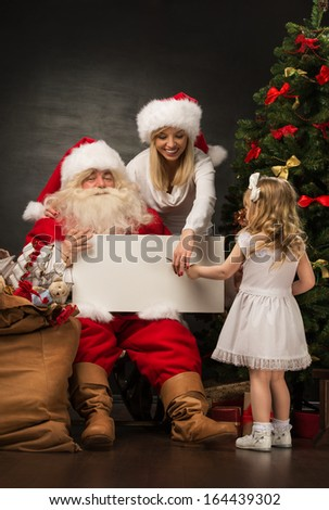 Santa Claus holding white blank sign with family - mother and her little daughter - stock photo