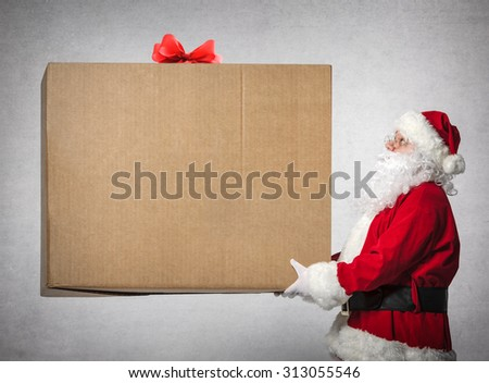 Santa Claus holds a big gift box with copy space for your text - stock photo