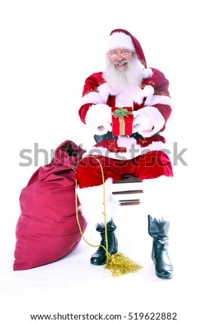 Santa Claus holds a red Christmas present with a bow. Isolated on white with room for your text.