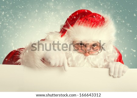 Santa Claus in a snow pointing to white blank banner - stock photo