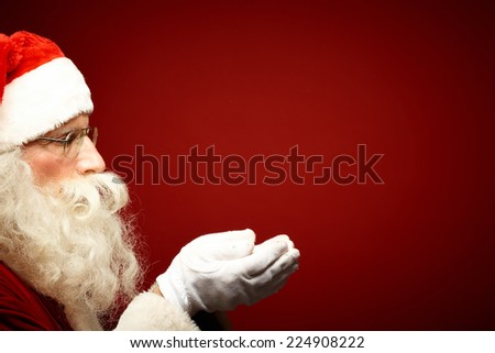 Santa Claus in eyeglasses holding snow on his palms