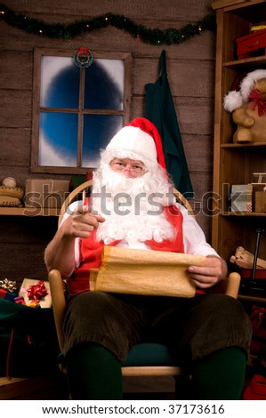 Santa Claus in Rocking Chair with Naughty List and Pointing at Viewer. Vertical Composition