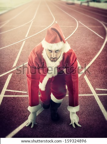 Santa Claus in the starting position on a running track. - stock photo