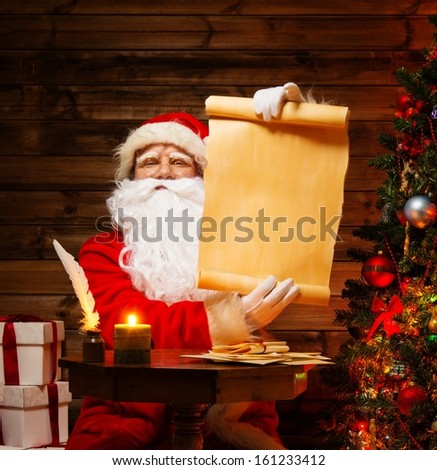 Santa Claus in wooden home interior holding blank wish list scroll - stock photo