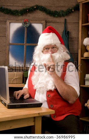 Santa Claus in Workshop Using Laptop and making Shh sigh at viewer. Vertical Composition - stock photo