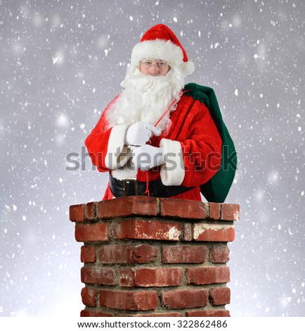 Santa Claus inside a brick chimney with his bag of toys flung over his shoulder. Vertical format with a snowy background.