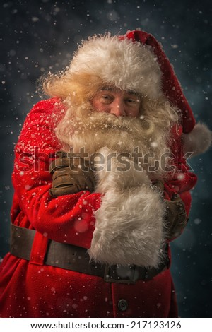 Santa Claus is feeling very cold standing outdoors at snowfall at north pole with hands folded - stock photo