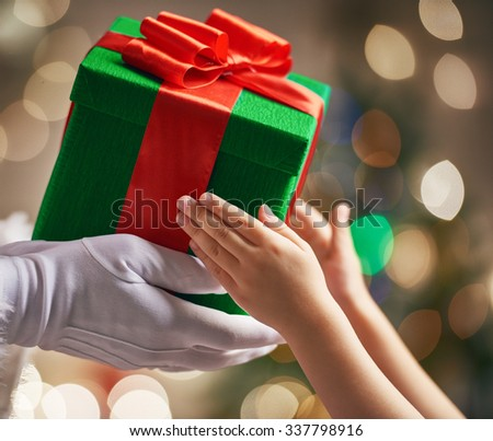 Santa Claus is giving a Christmas gift to child. - stock photo
