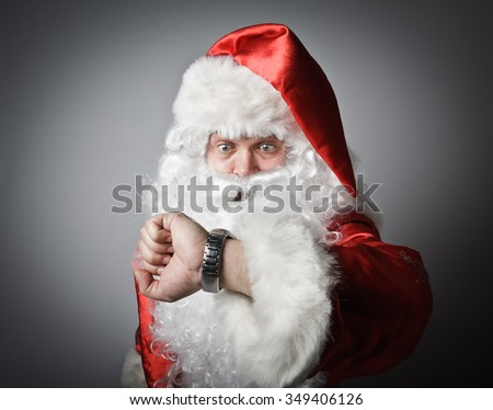 Santa Claus is looking at his wristwatch. Concept of being late. - stock photo
