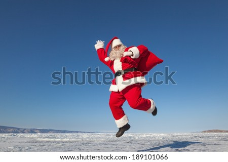 Santa Claus joyously jumping in the snow,  shooting was conducted in a sunny day on lake Baikal - stock photo