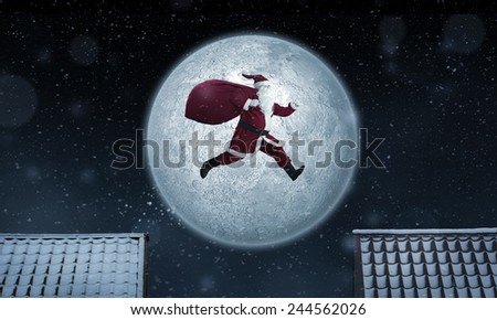 Santa Claus jumping between rooftops at night with bag full of gifts - stock photo