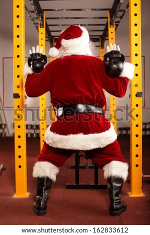 Santa Claus kettlebells training in gym, back view