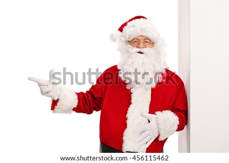 Santa Claus leaning against a wall and pointing with his finger to the left isolated on white background - stock photo