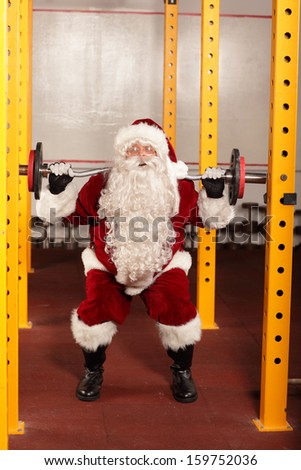 Santa Claus  lifting weights in gym - physical condition training before Christmas - stock photo