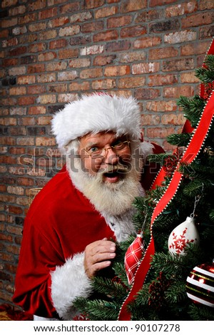 Santa Claus looking surprised as he is sneaking around the Christmas Tree with copy space above him. - stock photo
