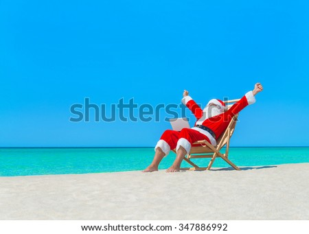 Santa Claus on deck chair hands up enjoy work using laptop computer at ocean sandy tropical beach - Christmas  and New Year vacation and travel destinations in hot countries concept - stock photo