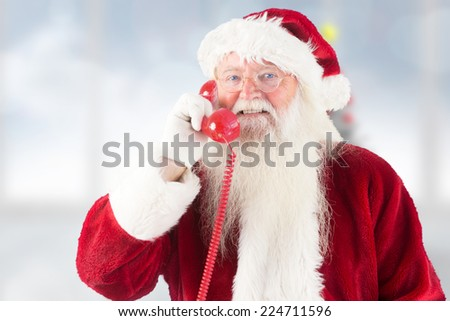 Santa claus on the phone against blurry christmas tree in room