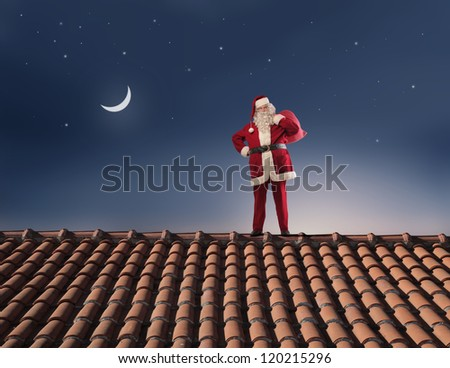 Santa Claus on the roof of a house with his sack full of presents - stock photo
