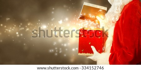 Santa Claus opening a red Christmas present on brown gold colored background - stock photo