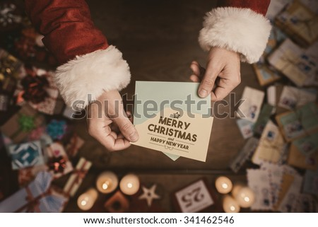 Santa claus opening an envelope and holding a Christmas card, hands close up, top view, desktop with gifts and letters on background - stock photo