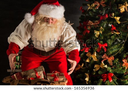 Santa Claus opening his sack and taking gifts under Christmas tree at night at living room at children's home