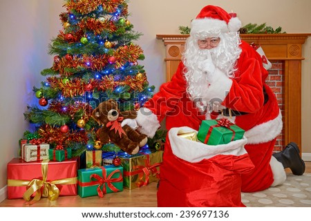 Santa Claus or Father Christmas putting presents under the tree whilst everyone is asleep. - stock photo
