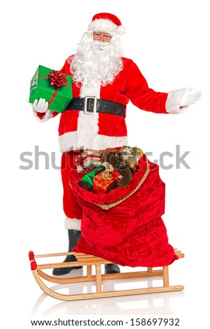 Santa Claus or Father Christmas with a sack full of gift wrapped toys and presents on a sled, isolated on a white background. - stock photo